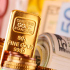 Gold bullion bar and paper currency.